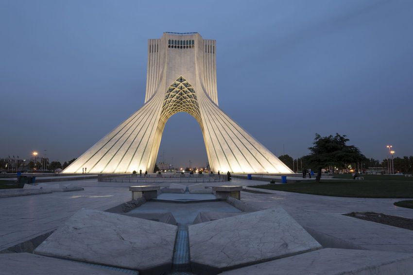 TEHRAN, IRAN - 7 May 2018 Azadi Tower at dusk time formerly known as the Shahyad Tower is a monument located at Azadi square and is an architectural landmark of Tehran Architecture Azadi Tower In Tehran Blue Hour Cityscape Building Exterior Built Structure City Clear Sky Day Dusk History Incidental People Landmark Lighting Memorial Modern Building Monument Nature Outdoors Pyramid Shape Reflecting Pool Sky The Past Tourism Travel Travel Destinations
