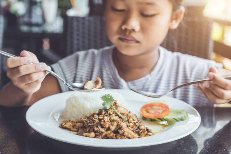 Close up Thai children eating in restaurant. Bored with food concept Childhood Eating Eating Utensil Focus On Foreground Food Food And Drink Fork Freshness Front View Glass Headshot Holding Indoors  Innocence Kitchen Utensil Meal One Person Plate Ready-to-eat Real People Spoon Table