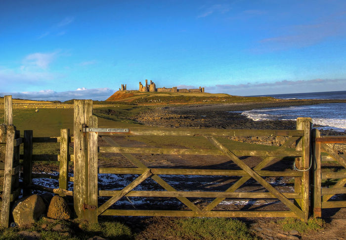 Farm land Castle Dunstanburgh Castle Farm Field Gate Barrier Beach Beauty In Nature Blue Castle On A Hill Clear Sky Craster Day Farm Gate Sheep Farm Fence Post Garden Gate Horizon Over Water Landscape Nature No People Outdoors Scenics Sea Sky Wood - Material
