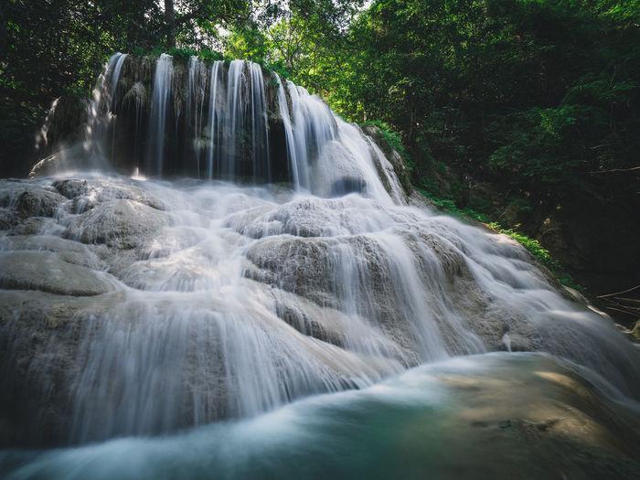 Scenic waterfall smooth stream in rainforest. bottom up angle. erawan falls, kanchanaburi, thailand.