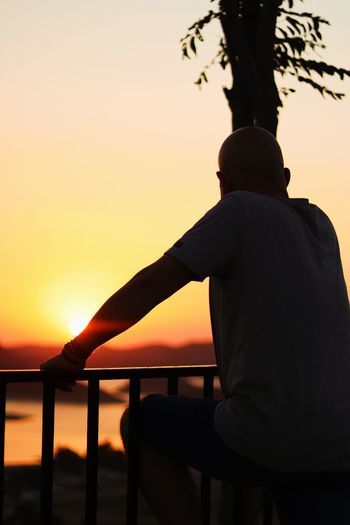 Rear view of silhouette man sitting by railing against orange sky