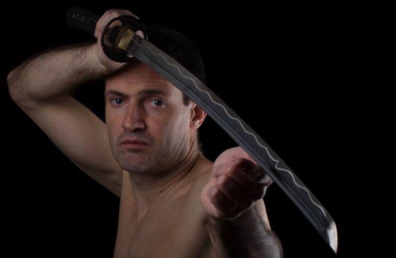 Close-up portrait of shirtless man holding sword over black background
