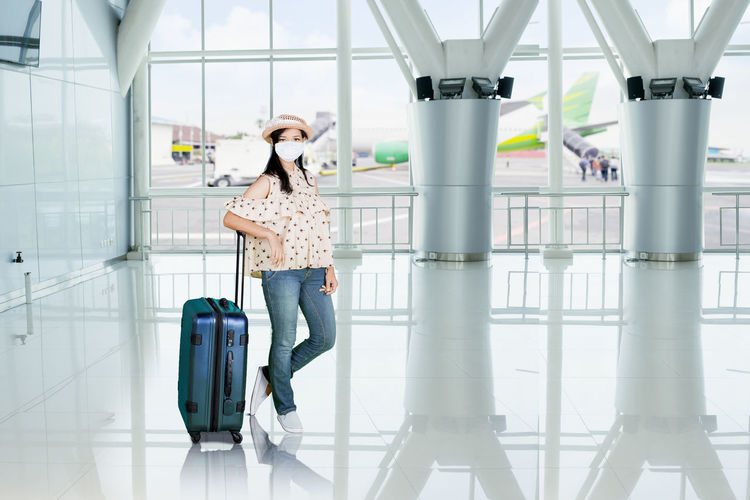 Portrait of woman wearing mask holding suitcase at airport