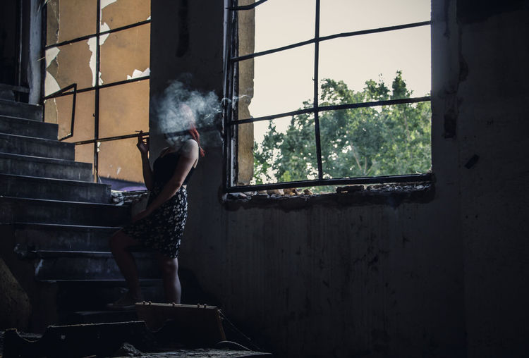 Young woman smoking while standing on steps in abandoned building