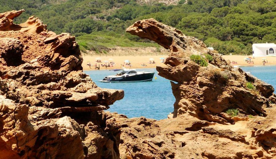Motorboat in sea seen through rock formation
