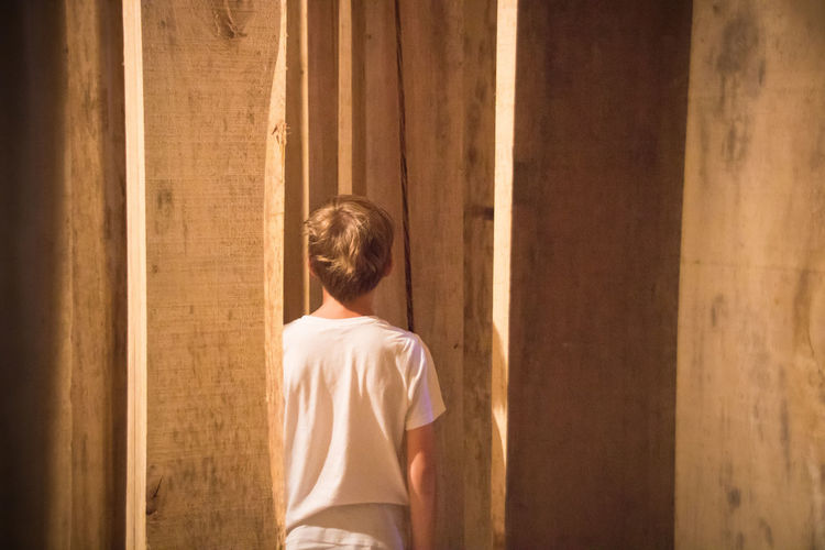 Rear view of boy standing amidst wooden planks