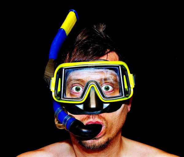Funny photo of a man with diver mask and snorkel Man Diving Diver Fun Funny Humor Underwater Problem Finance Psychology Studio Eyes Shocked Shock Surprised Surprise Mask Snorkeling Laughing Observe Fear Anger View Face Stock