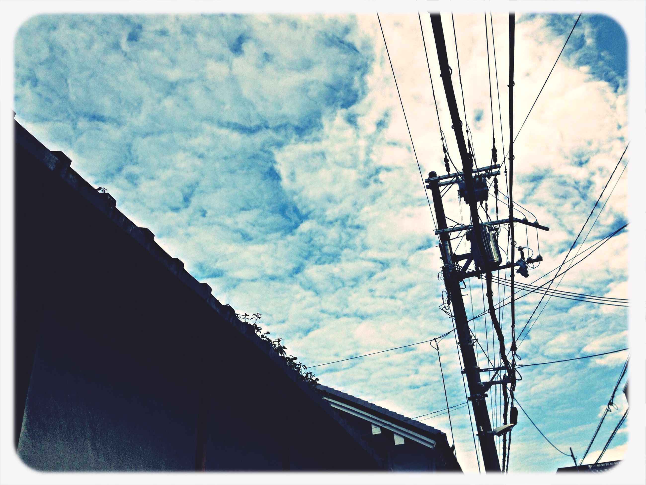 low angle view, transfer print, sky, power line, auto post production filter, cloud - sky, built structure, architecture, electricity pylon, cloudy, power supply, electricity, connection, cable, building exterior, cloud, technology, fuel and power generation, outdoors, silhouette