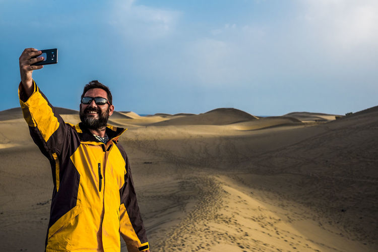 man traveler take a selfie picture using the smartphone with a desert and ocean in background. adventure and alternative vacation concept for caucasian people. enjoy life and freedom and nature contact Adult Arid Climate Climate Color Communication Desert Holding Land Leisure Activity Lifestyles Men Nature One Person Outdoors Photographing Photography Themes Real People Sand Scenics - Nature Selfie Sky Standing Technology Wireless Technology Young Man