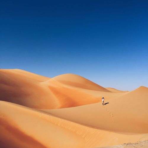 Distant view of man walking on sand dune in desert against clear blue sky