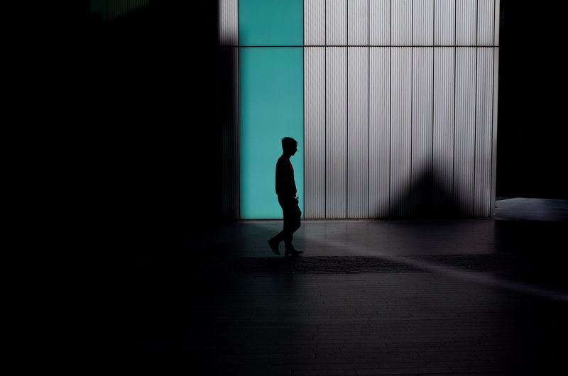 Side view of silhouette man walking against building with shadows