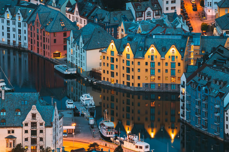 High angle view of illuminated buildings by canal in city