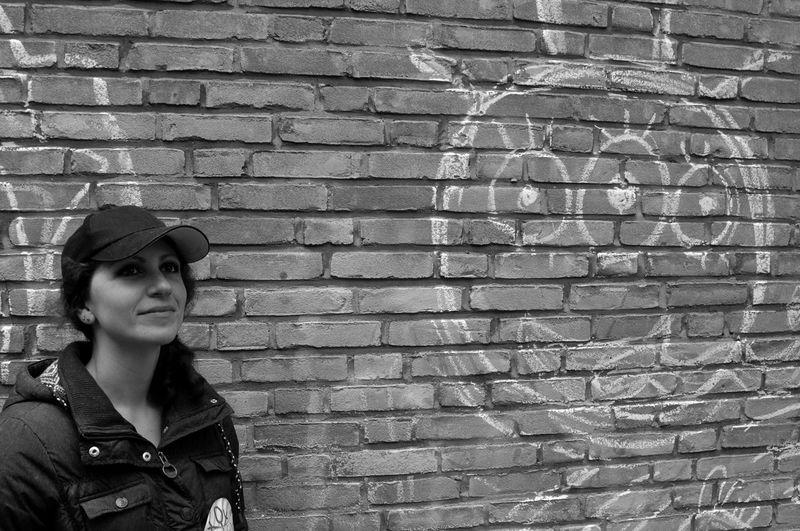 Woman Standing Against Graffiti On Brick Wall