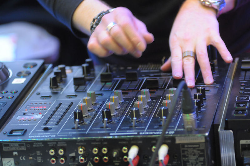 Midsection of man operating sound mixer in club