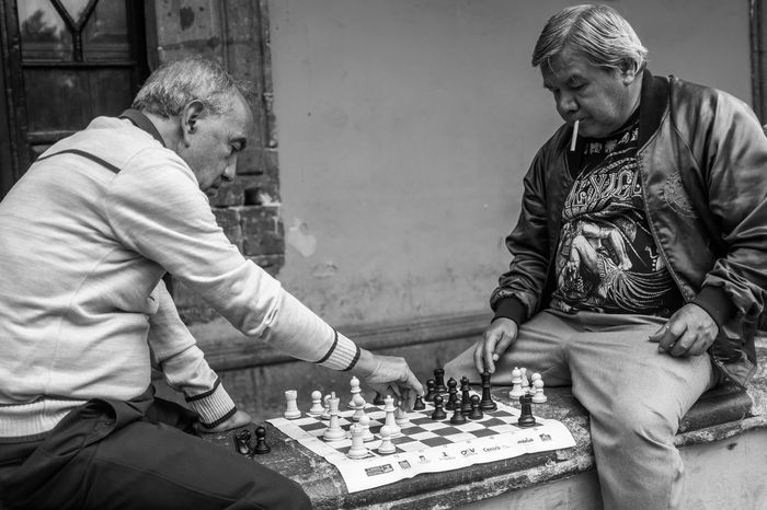 A game of Chess: Cigarettes Mexico Smoking Board Game Casual Clothing Chess Chess Piece Cigar Cigarette  Fuji Fujifilm Game Mexican Mexicans Playing Senior Adult Sitting Street Street Photography Streetphoto_bw Streetphotography Stretphotography Two People Week On Eyeem X100f