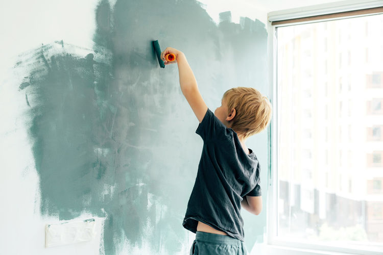 Rear view of boy painting on wall at home