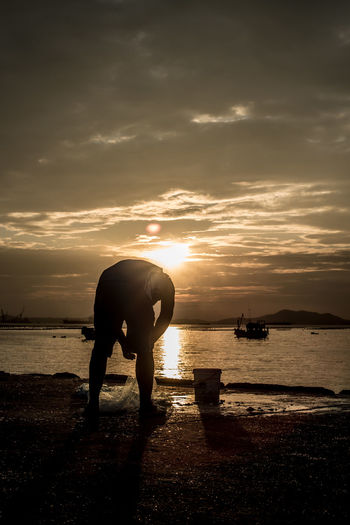 Fisherman with fishing net on jetty at sea Dark Day Escapism Fisherman Fishing Folkways Jetty Light Light Man Nature Ocean Outdoors Port Sea Sea And Sky Silhouette Silhouette_collection Sky Street Photography Sunset Time Thailand Weekend Activities Working
