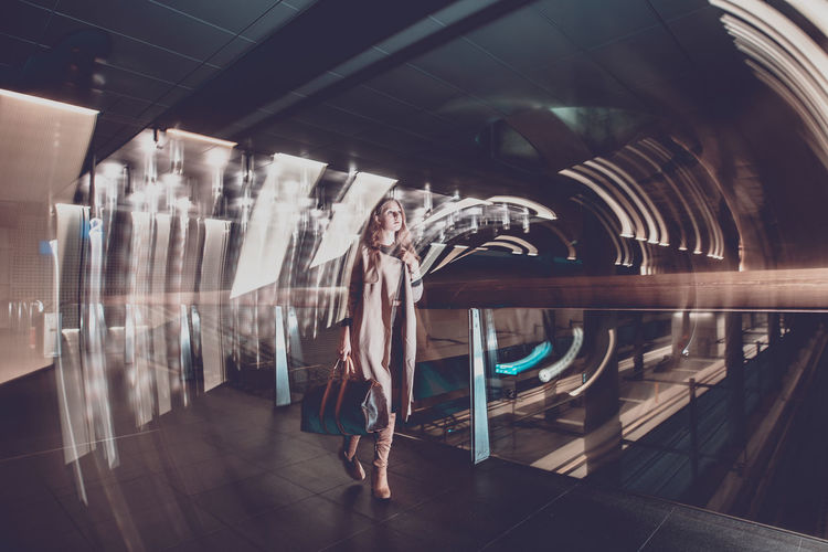 Double exposure of woman walking in illuminated corridor