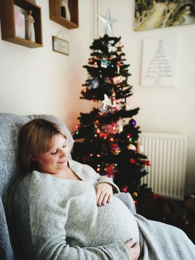 Pregnant woman sitting by christmas tree at home