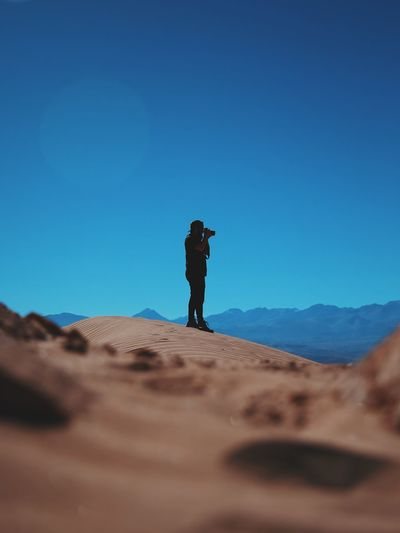 Man photographing at atacama desert against clear blue sky
