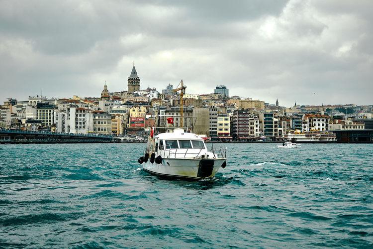 Boat in sea against buildings in city