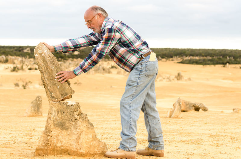 Side view of senior man holding broken limestone at the pinnacles in nambung national park