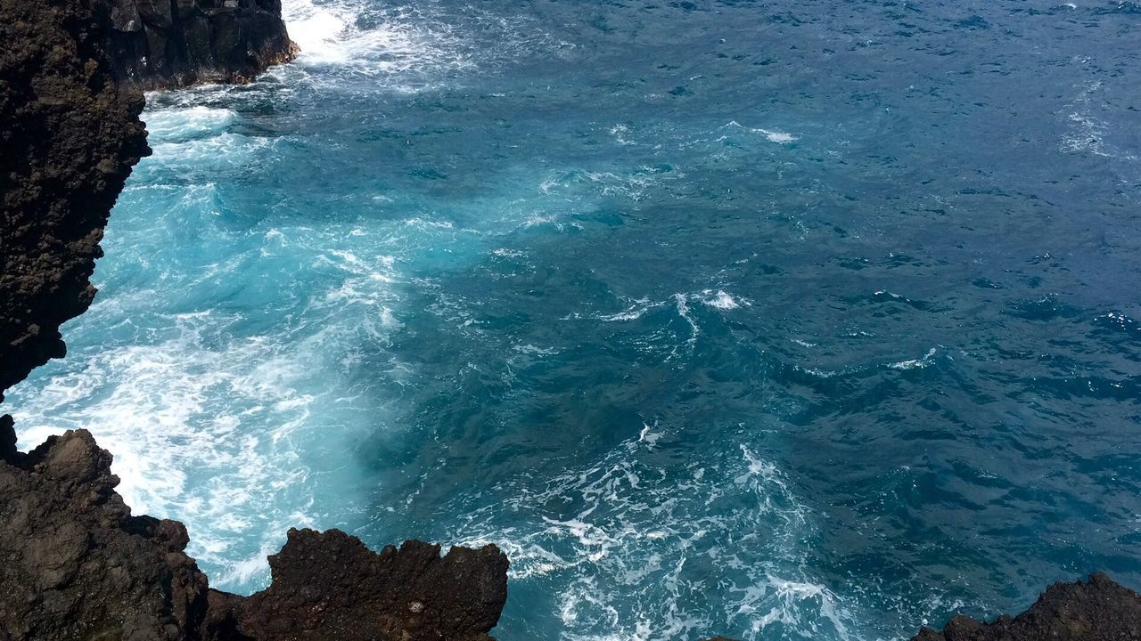 sea, water, rock, beauty in nature, solid, rock - object, nature, no people, motion, rock formation, scenics - nature, day, wave, blue, high angle view, outdoors, land, beach, aquatic sport, power in nature, turquoise colored