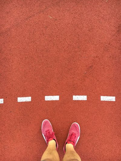 Low section of man standing on running track