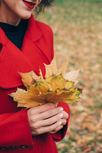 Midsection of woman holding autumn leaves