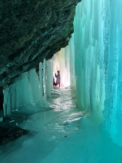 Friends Standing In Ice Cave