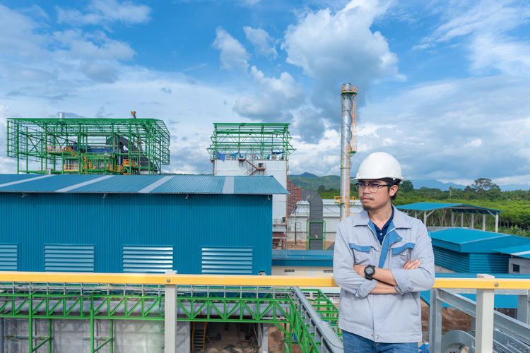 Power Plant Architecture Cloud - Sky Day Engineer Front View Hardhat  Industry Leisure Activity Lifestyles Men Nature Occupation One Person Outdoors Railing Real People Sky Standing Young Adult Young Men