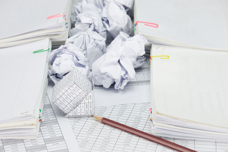 High angle view of crumpled paper balls with model house on financial documents
