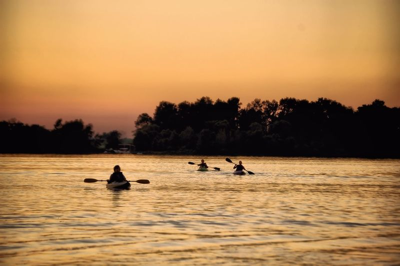 Silhouette of people rafting on river