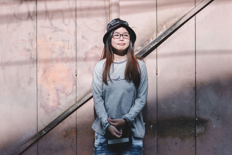 One Person Young Adult Casual Clothing Standing Front View Young Women Wall - Building Feature Clothing Lifestyles Three Quarter Length Real People Architecture Day Portrait Leisure Activity Hair Hairstyle Looking At Camera Outdoors Beautiful Woman Hood - Clothing