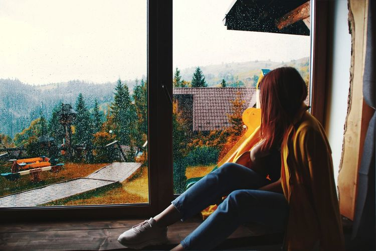 Woman looking through window while sitting at home during rainy season