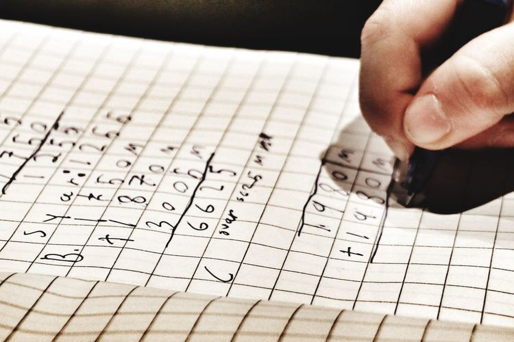 Cropped hand of person solving mathematics problems on paper