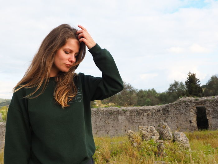 Young woman looking away from camera against sky