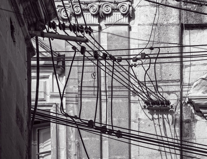 Wired Architecture Building Exterior Built Structure Confusion Day Electricity  Function No People Outdoors Stone Tangle Telephone Wires