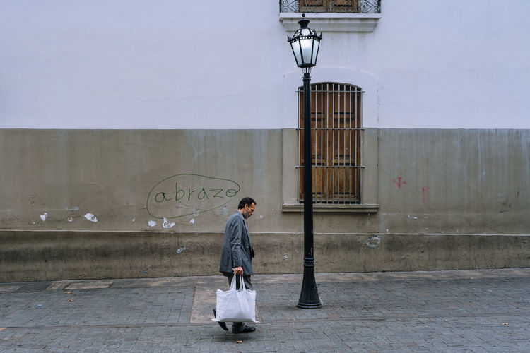 Full length side view of a woman walking against building