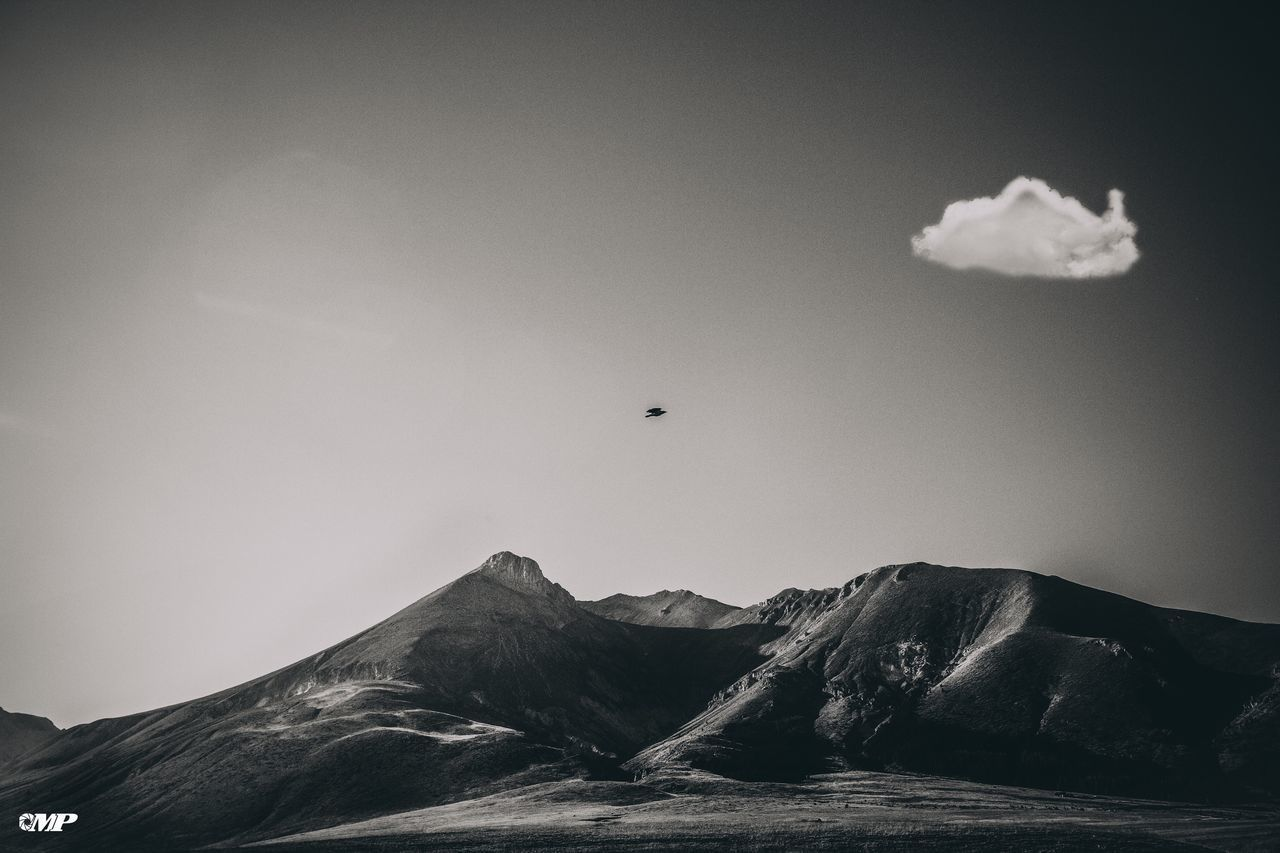sky, mountain, vertebrate, cloud - sky, beauty in nature, scenics - nature, animal themes, bird, animal, no people, nature, tranquil scene, day, one animal, tranquility, flying, animals in the wild, animal wildlife, mountain range, mid-air, outdoors, mountain peak, formation