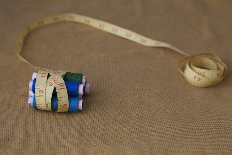 Close-up of threads wrapped in tape measure on table