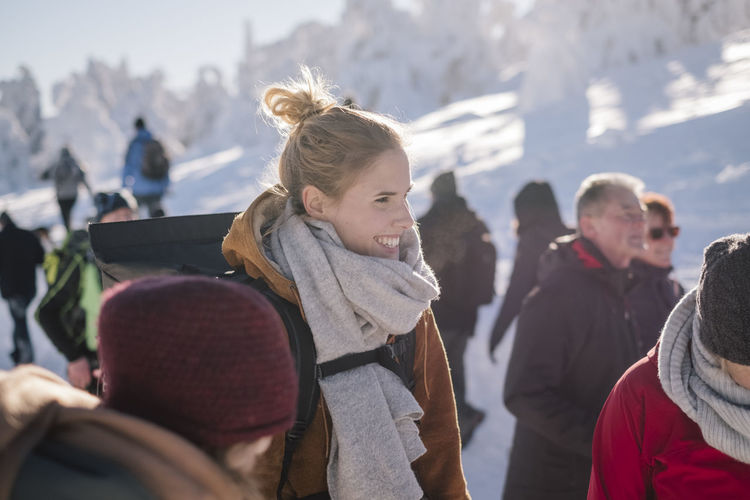 Smiling young woman wearing warm clothing while looking away by people in winter