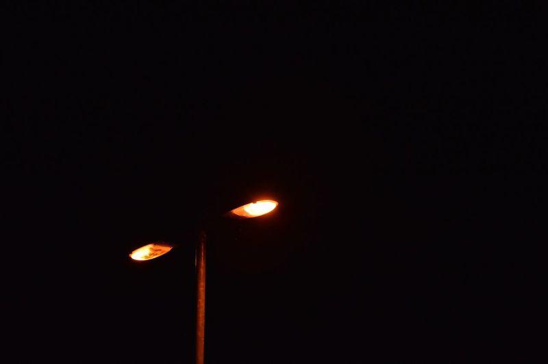 Low angle view of illuminated lighting equipment at night