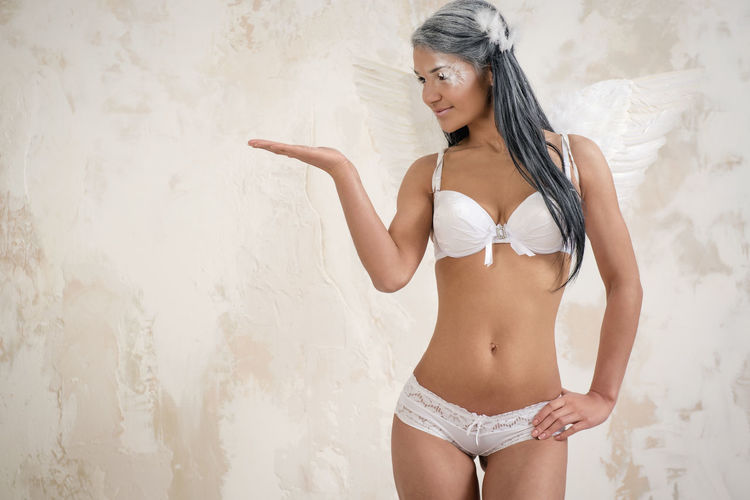 Young woman as angel showing something with the hand over white obsolete background Fairy Makeup Myth Wall Woman Angel Angel Wings Attractive Beautiful Woman Brunette Gesturing Indoors  Lingerie Long Hair Model Mythology One Person Pose Posing Sexygirl Showing Studio Shot Underwear😈 Young Adult Young Women