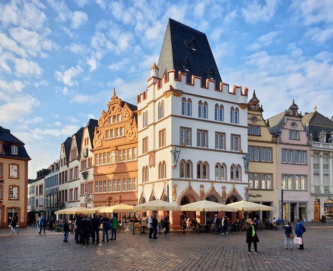 People on street by buildings in town against sky