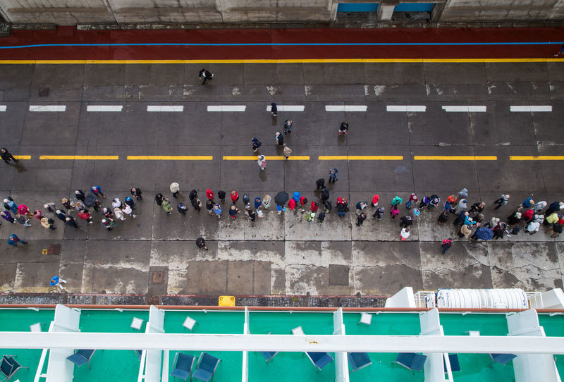 Cruise Ship Day High Angle View Large Group Of People Long Queue Off The Ship Outdoors Shot From Above  Starting To Rain Waiting For A Taxi