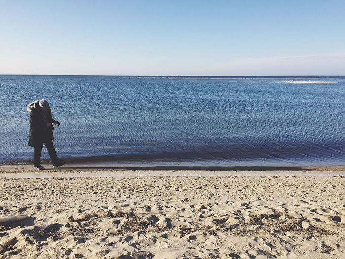 Full Length Of Man In Warm Clothing Walking At Sea Shore Against Sky