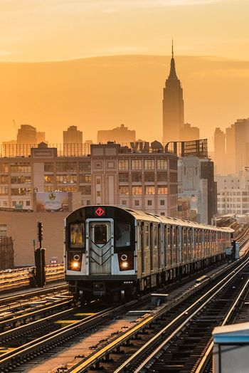 Sunset glow 🌇. View of Empire State Building from Queens, New York. New York City New York NYC Empire State Building Rail Transportation Track Train Transportation Mode Of Transportation Architecture Railroad Track Train - Vehicle Public Transportation Sunset City Commuter Travel Destinations The Traveler - 2019 EyeEm Awards