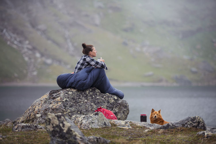 Man sitting on rock at shore against mountains