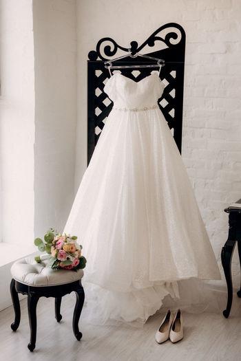 Wedding dress hanging on coat hanger against white wall